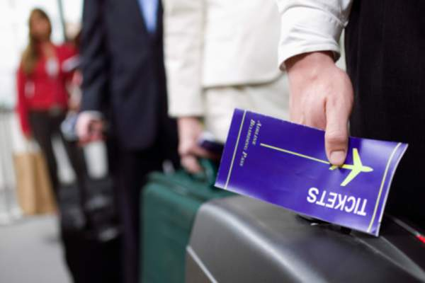 Person holding a plane ticket.