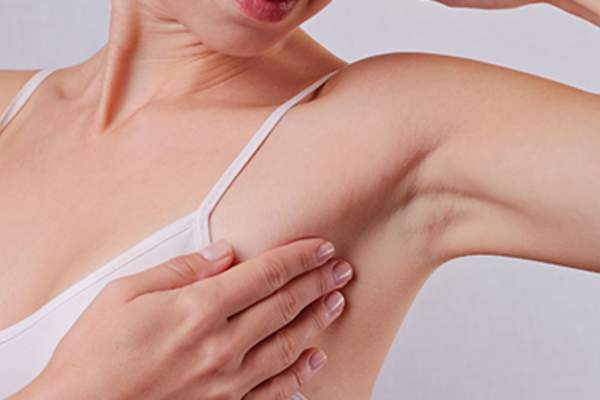 Woman touching her armpit.