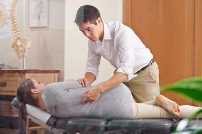 Chiropractor examining a woman's spine.