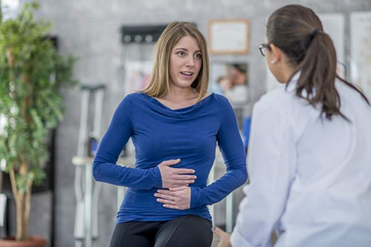 Woman and doctor discussing symptoms.