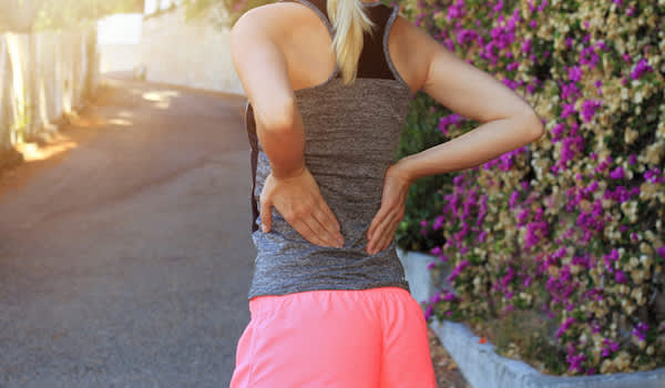 Woman with lower back pain while on morning walk.
