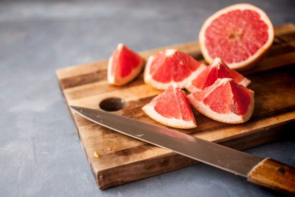 grapefruit and knife on cutting board