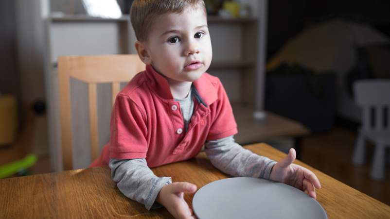 Young boy with an empty plate at the table.