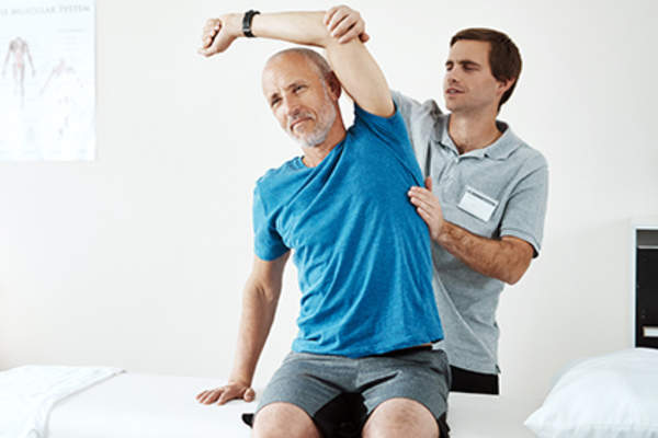 Helpful chiropractor helping diabetic man with joint pain.