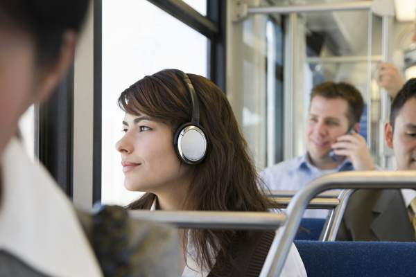 Woman listening to headphones while commuting to work on the train.