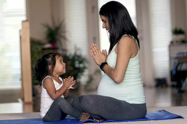 pregnant mom and daughter meditating image