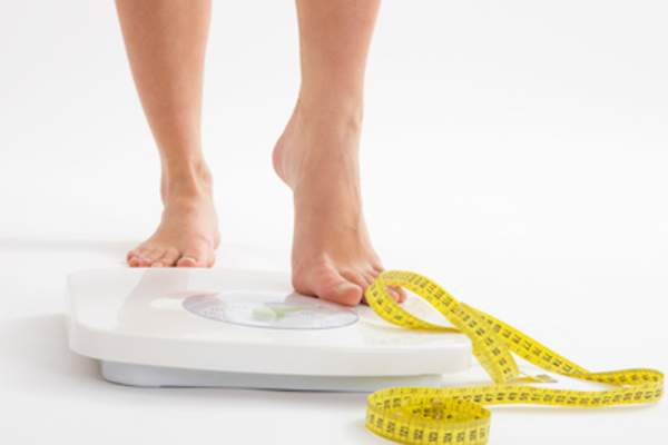 continued weight loss concept, stepping on scale with measuring tape.