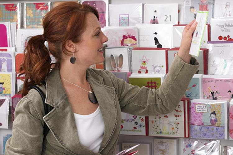 Woman looking at greeting cards on rack.