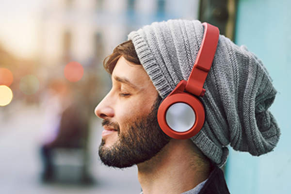 Relaxed man listening through headphones.