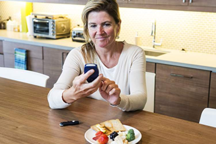 A diabetic woman checks her blood sugar before a meal.