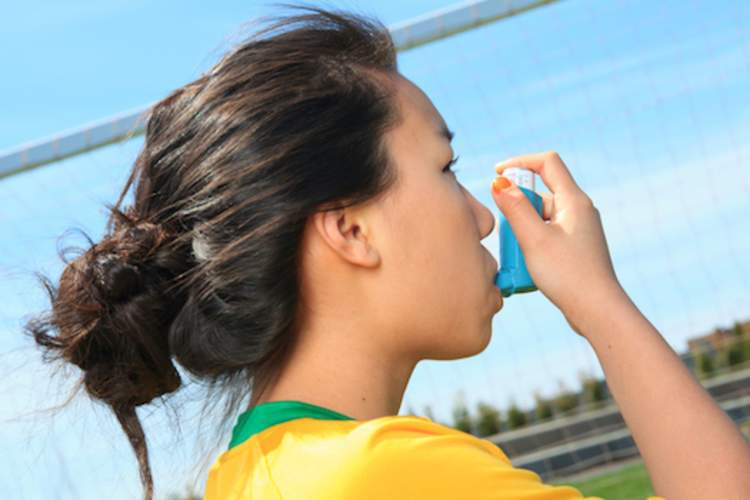 Grade school student using inhaler on soccer field.