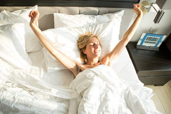 Woman waking up well rested in bed.