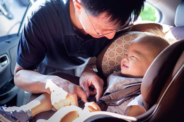Smiling father putting baby in car seat.