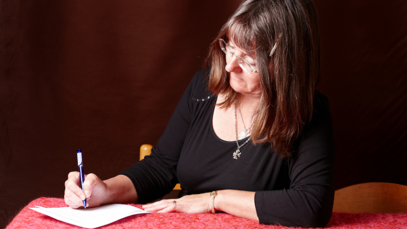 Middle aged woman writing letter