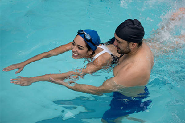 Smiling woman taking swim lesson from male instructor.