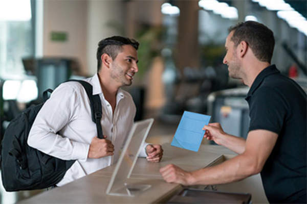 Man talking to trainer at gym desk about an exercise program.