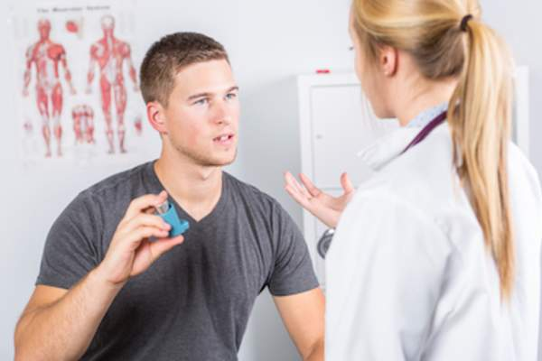 Patient talks to doctor about inhaler.