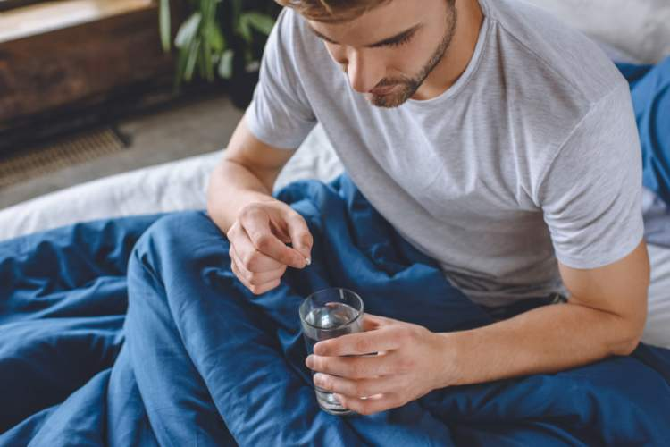 man in bed taking small white round pill