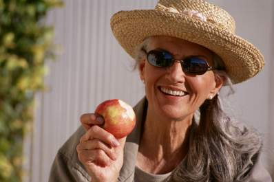 Woman enjoys apple as part of a high fiber diet.