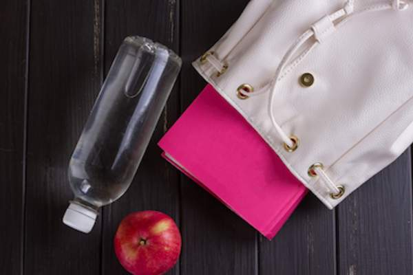 Water, apple , and a book with bag.