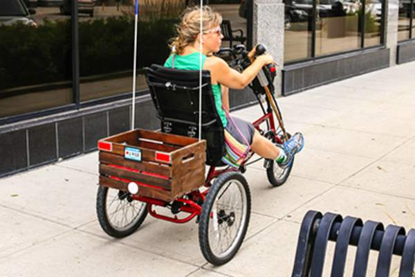 Woman riding adult tricycle.