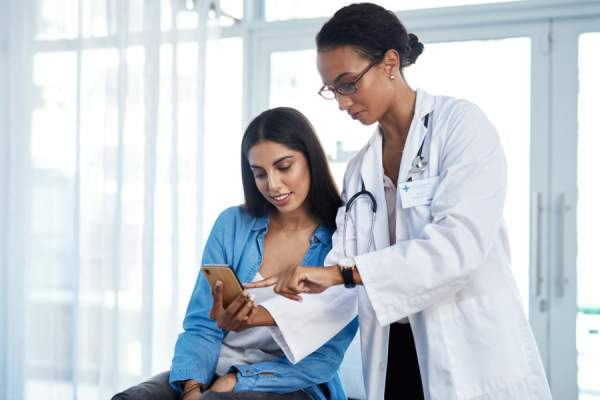 doctor showing patient something on phone