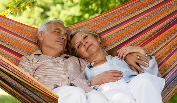 Senior couple sleeping outside in a hammock.