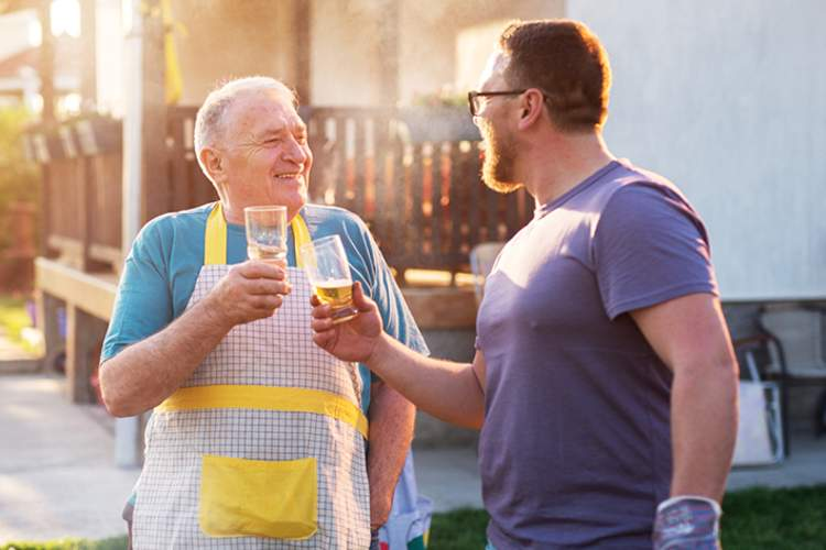Senior man and adult son having a beer at a barbeque.