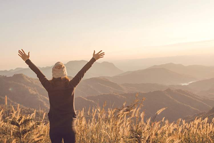 Woman raising her arms in the air while overlooking at mountainous landscape.