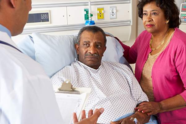 Doctor explaining diagnosis to senior African American couple.