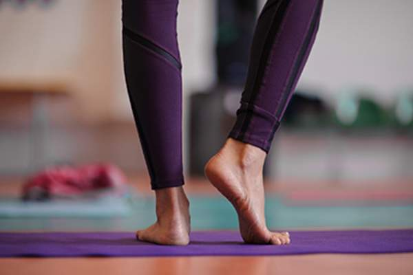 Woman standing barefoot at yoga class.