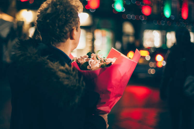 man holding flowers on city street at night