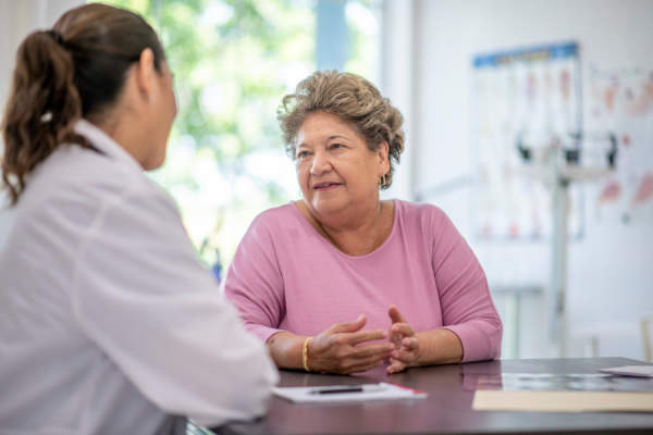 senior woman talking to doctor, gesturing
