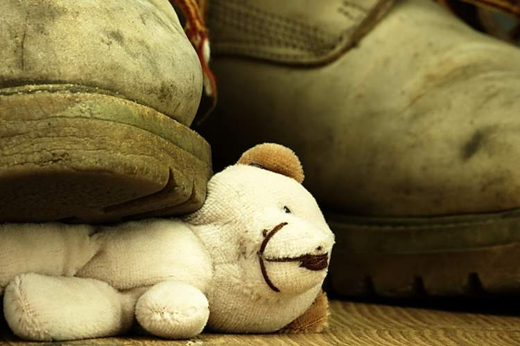 Childhood abuse, a boot stepping on a teddy bear.