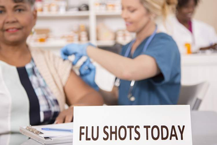 Woman getting flu shot at pharmacy counter image.