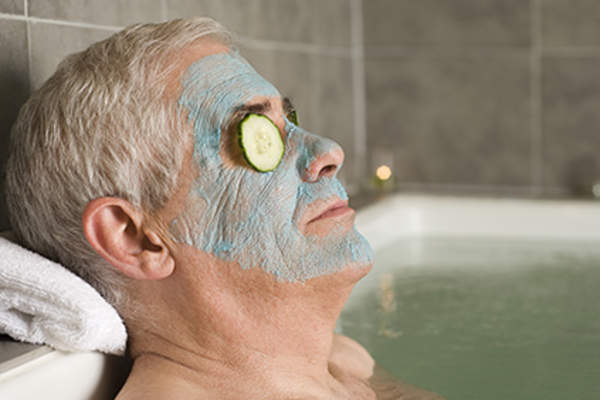 Man wearing a face mask relaxing in the bath.