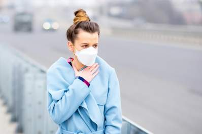 Young woman wearing face mask in air pollution.