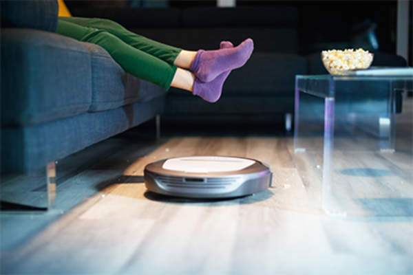Robot vacuum, person watching television raising their feet.