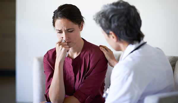Doctor supporting anxious woman.