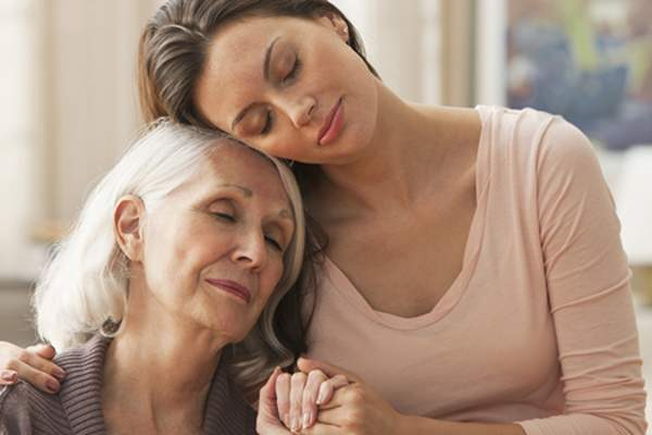 Woman comforting senior mother image.
