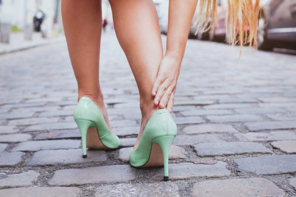 Blisters, woman on high heels has difficulties to walk