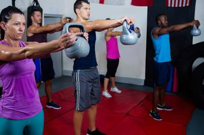 People lifting kettle weights at a gym image.