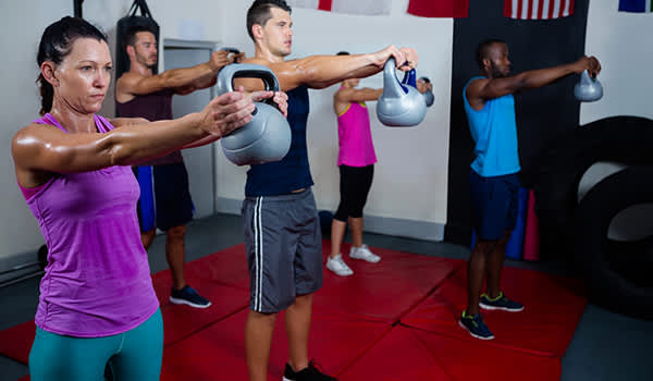 People lifting kettle weights in a gym image.