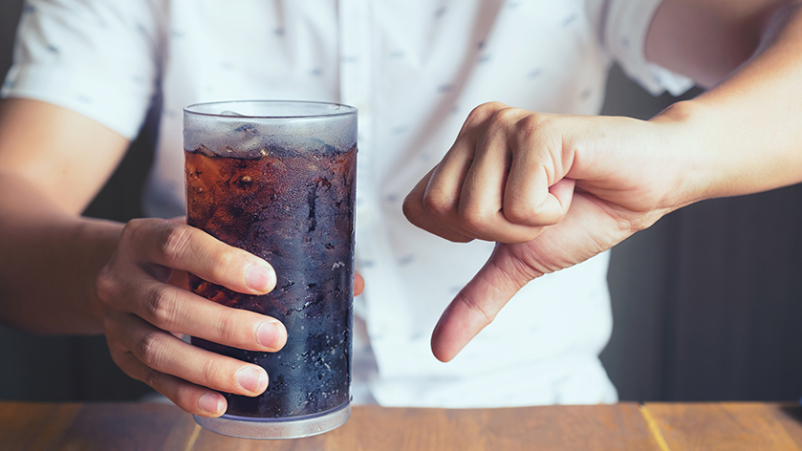 Man holding a glass of soda with a thumb-down.