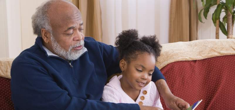 man reading to granddaughter