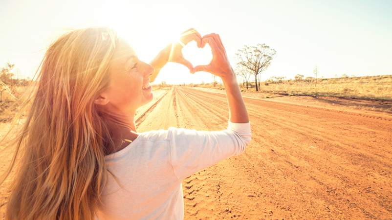 Woman holding up heart-shaped hands in the desert.