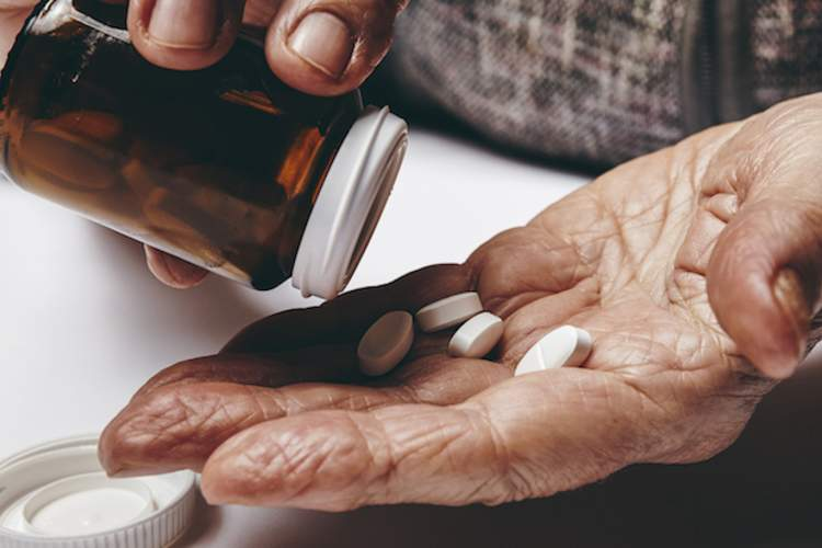 Elderly man taking medication.