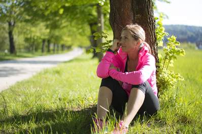 Woman taking a break from exercise by resting against a tree