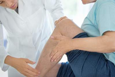 Doctor looking at the skin on a woman's lower leg.