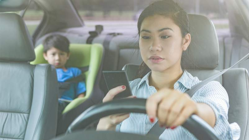 Mother driving and using cell phone while child is in back seat.